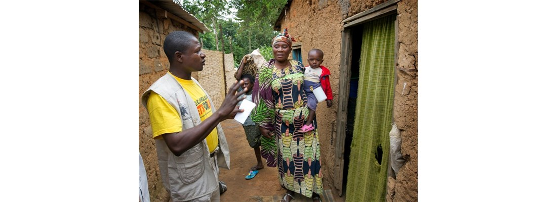 Health worker talks with Sophie Fragamga and son before a nets distribution in Bogonga.