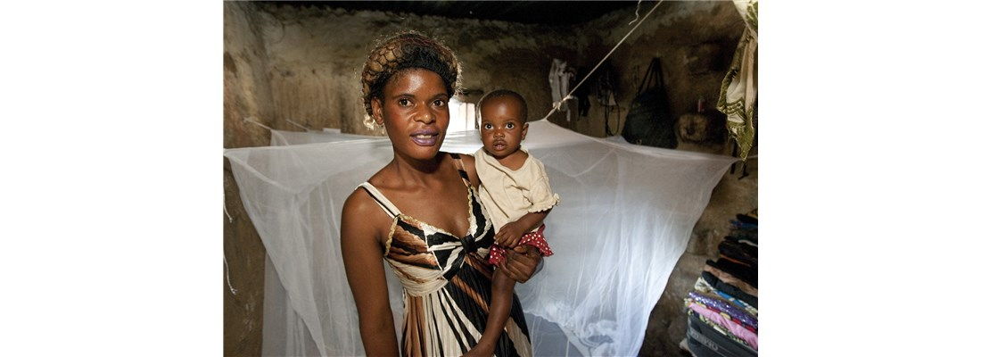 Natalie Naman holds daughter Dunongo in front of the mosquito net her family received during an interfaith nets distribution.